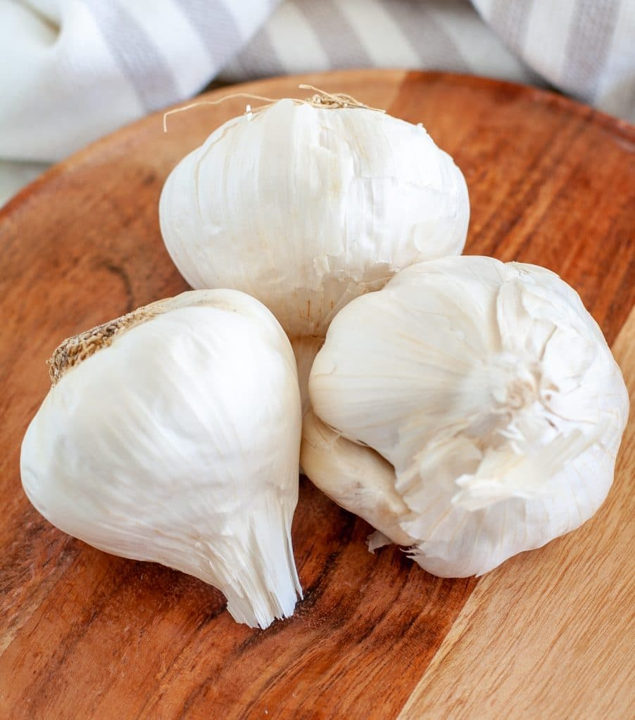 Three heads of garlic on plate.