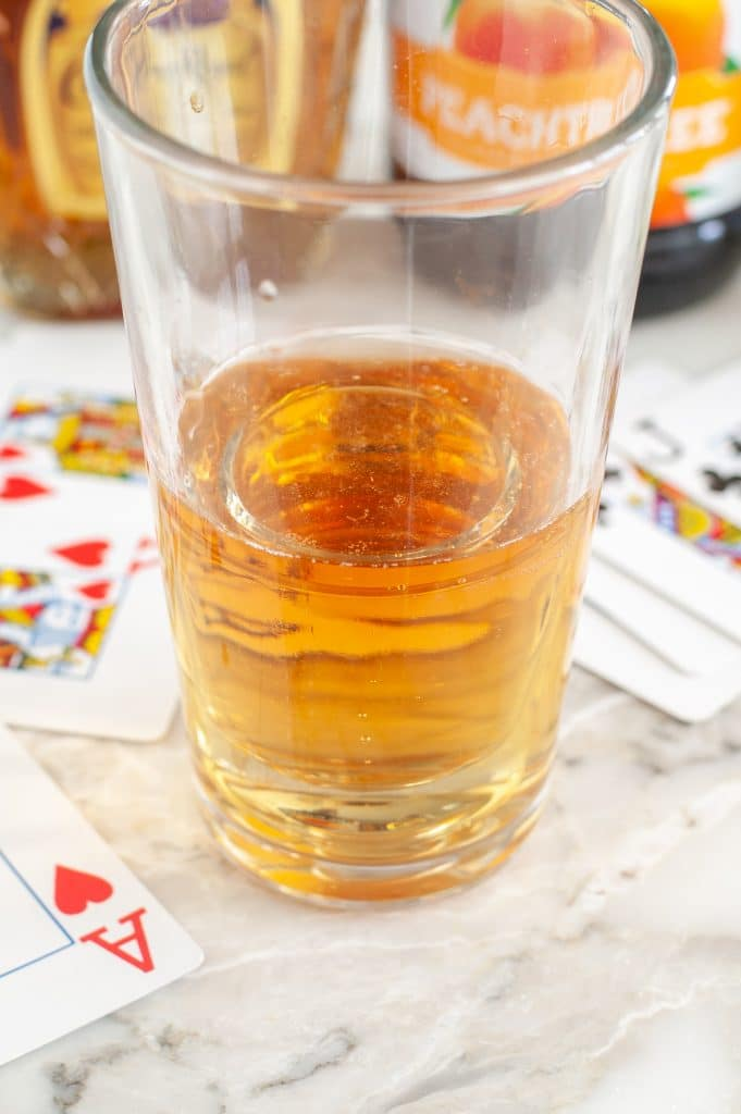 Glass with energy drinks and playing cards beside the glass.
