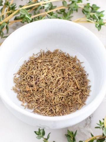 Dried thyme in a bowl with fresh thyme on a table.