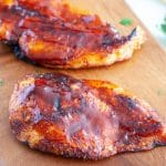 Cooked chicken breast on cutting board.