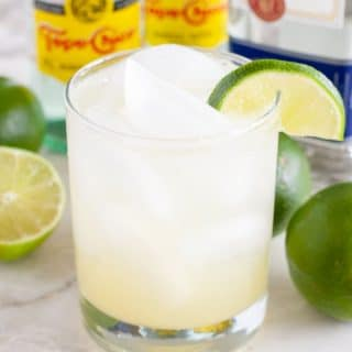Clear drink in a glass with lime wedge.