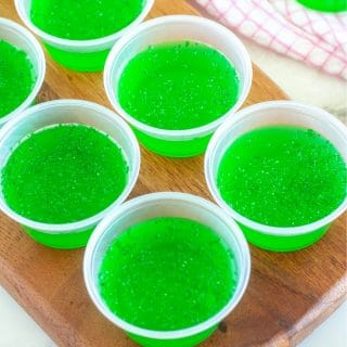 Board with cups of green jello.