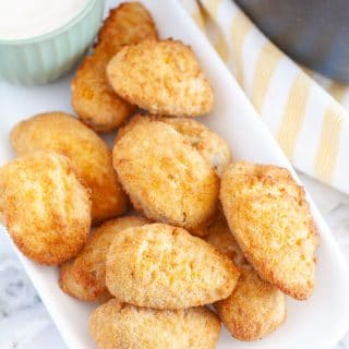 Jalapeno poppers on a plate with bowl of ranch.