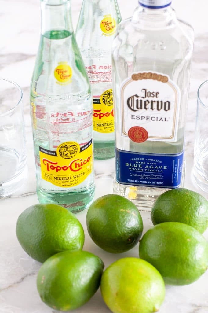 Bottle of Topo Chico, tequila and limes.