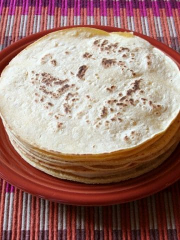 Stack of tortillas on a plate.