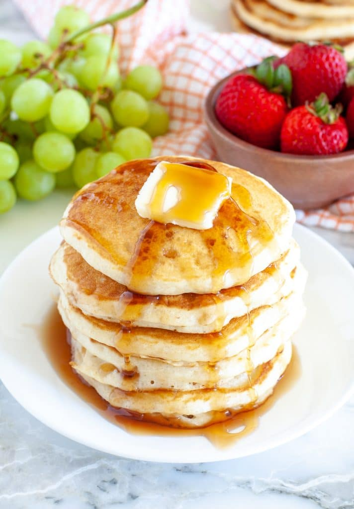 Plate with a stack of pancakes and syrup.