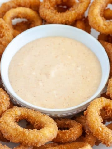 Bowl of sauce surrounded by onion rings.