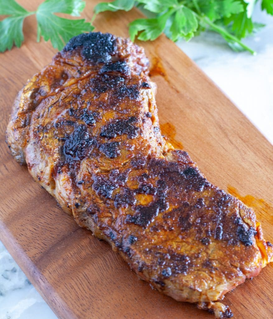 Cooked steak on cutting board.