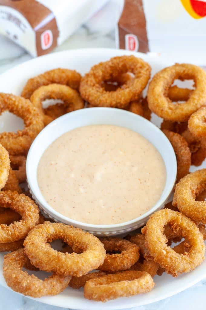 Sauce in a bowl surrounded by fried onion rings.