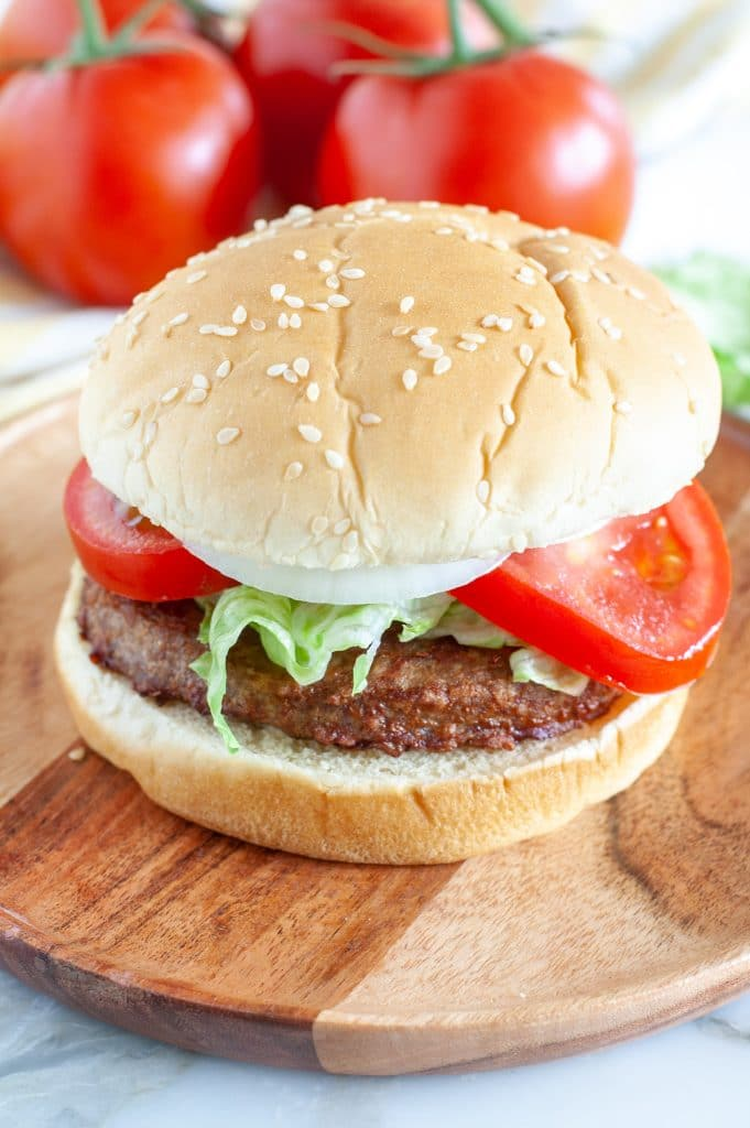Burger on a plate with tomatoes in background.
