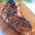 Seasoned steak on a cutting board.