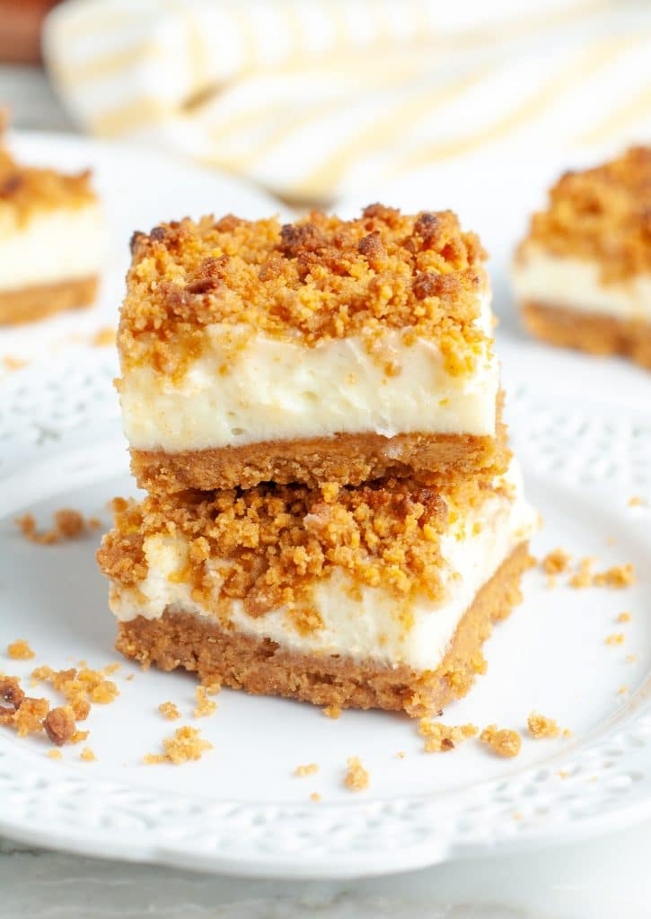 Two cheesecake bars stacked on plate.