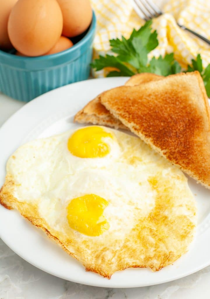 Two fried eggs on a plate.