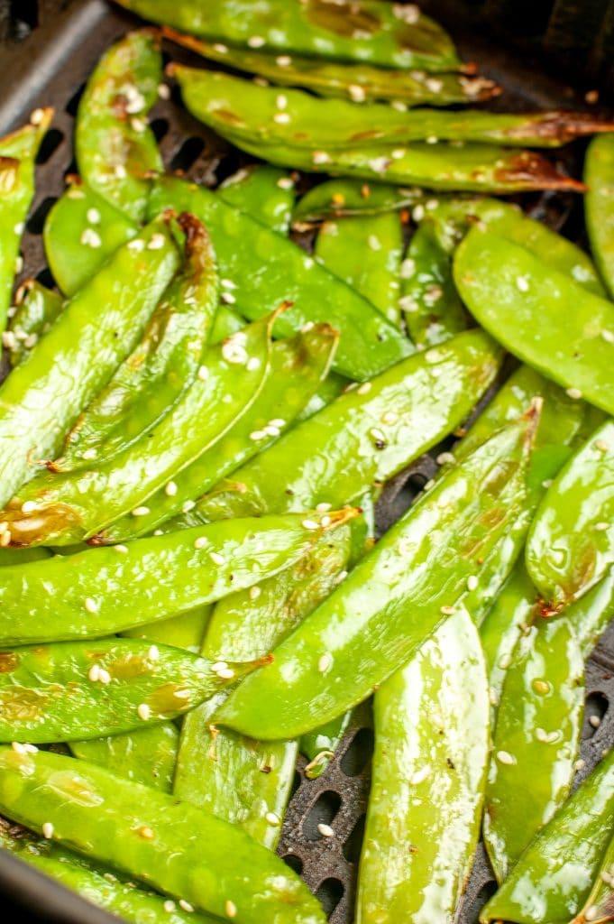 Cooked peas in air fryer basket.