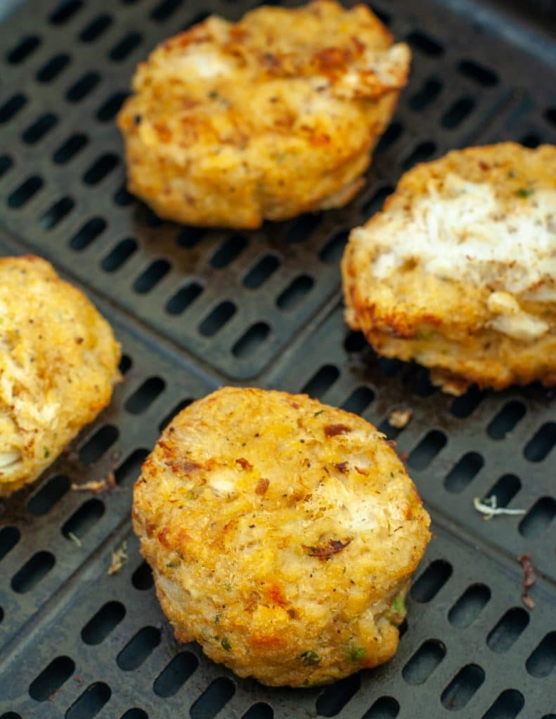 Cooked crab cakes in air fryer basket.