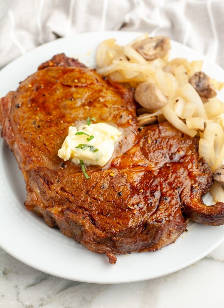 Steak on a plate topped with butter.