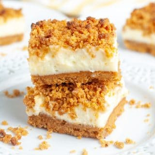 Dessert bars with crumb topping stacked on plate.