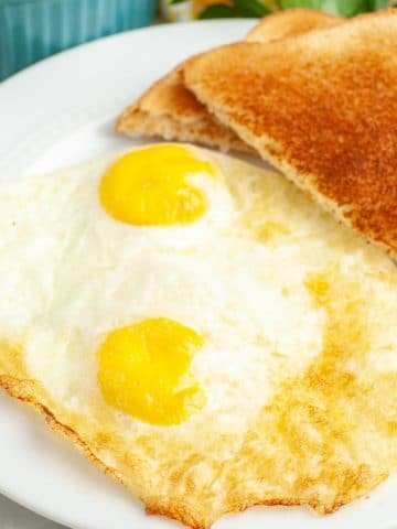 Cooked eggs on plate with toast.