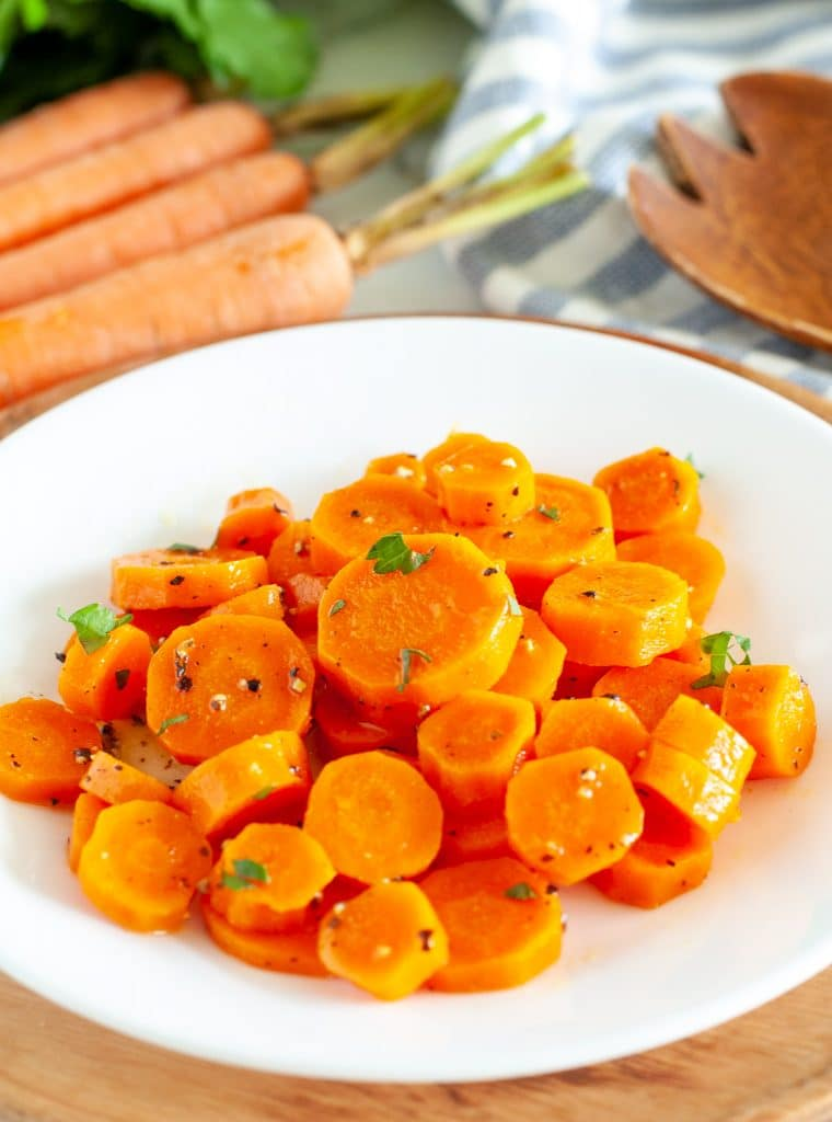 Cooked sliced carrots on a plate.
