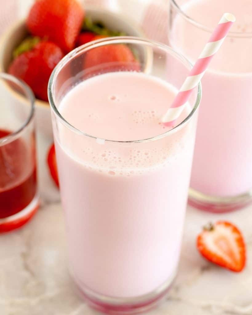 Glasses of milk with bowl of strawberries.