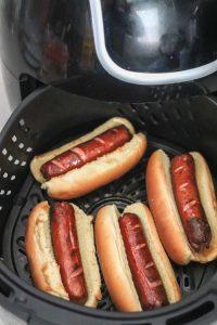 Hot dogs in air fryer basket.