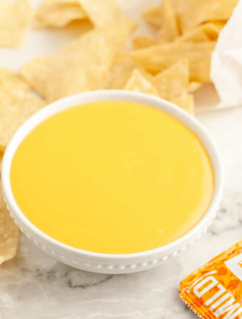 Small bowl with cheese sauce and tortilla chips.