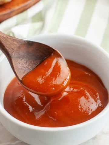 Bowl of red sauce and a wooden spoon.