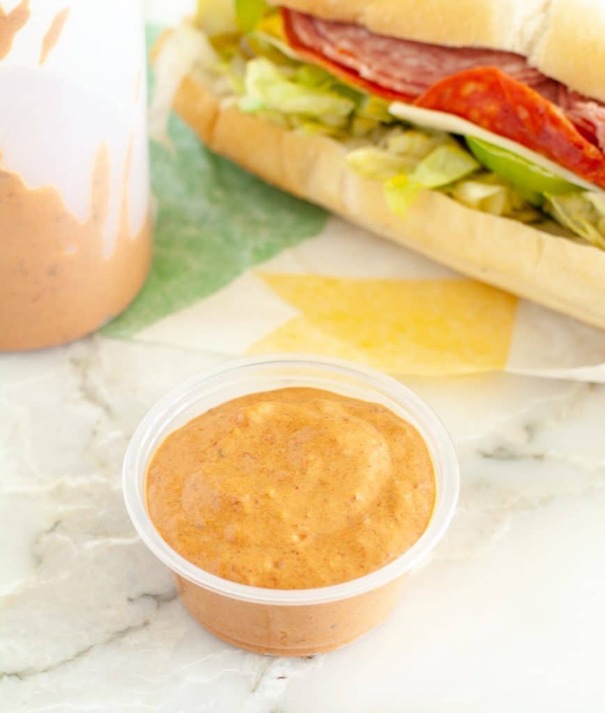 Cup of sauce and sandwich.