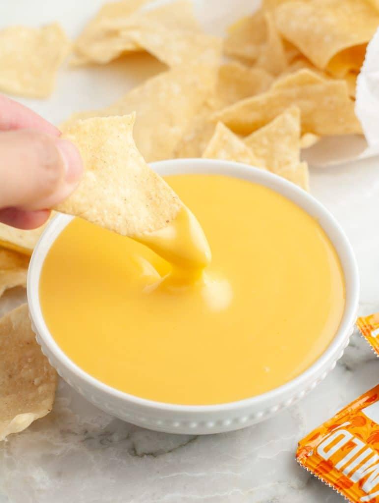 Bowl of cheese sauce with chip.