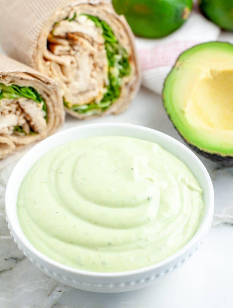 Bowl of green sauce with half an avocado.