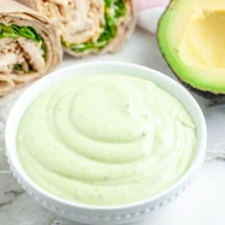 Green dressing in a bowl with chicken wrap.