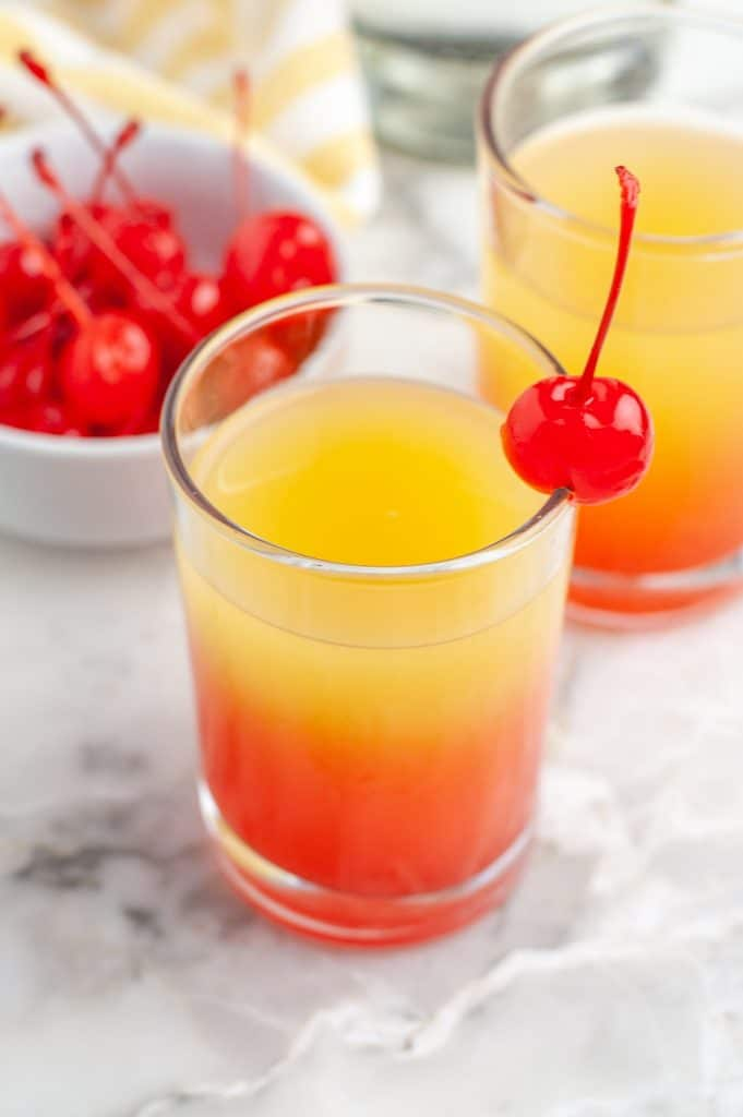 Glass with juice and a cherry on top.