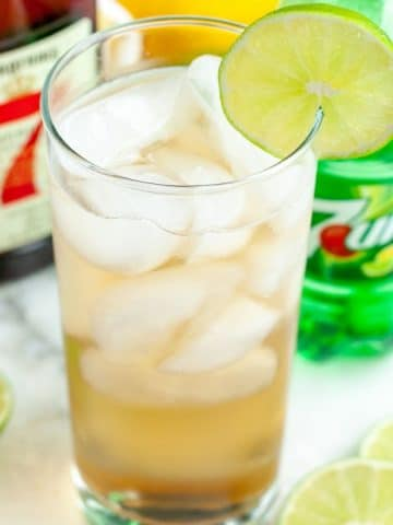 Glass filled with a drink and lime slice.