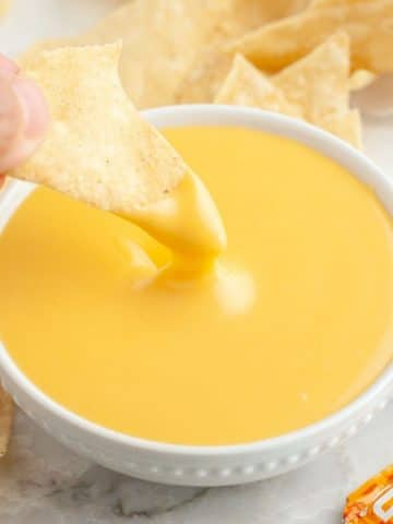 Chip dipped into cheese sauce.