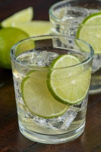 Glass with gin and lime slices.