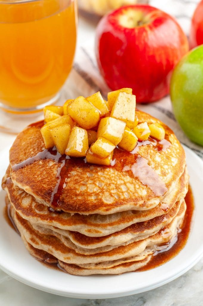 Stack of pancakes topped with diced apples.