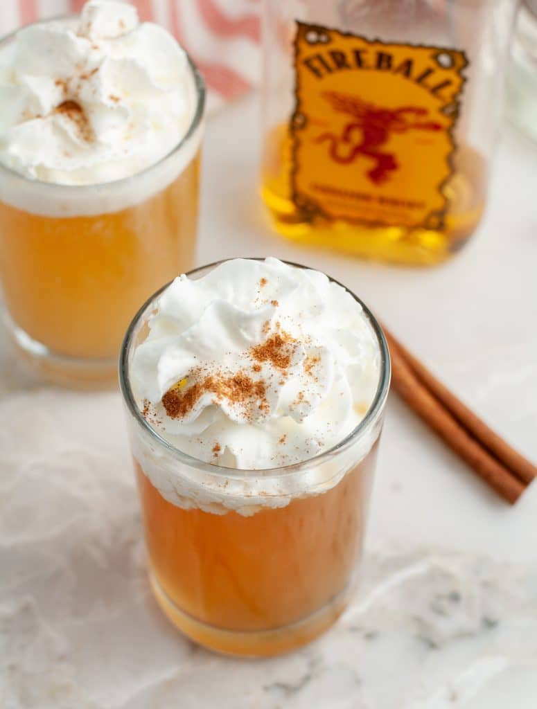 Glass with apple cider and whipped cream.