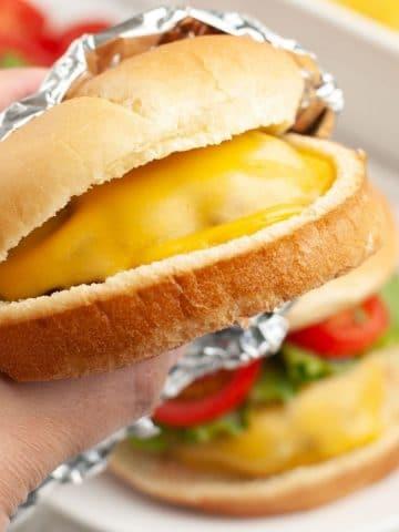 Hand holding cheeseburger.