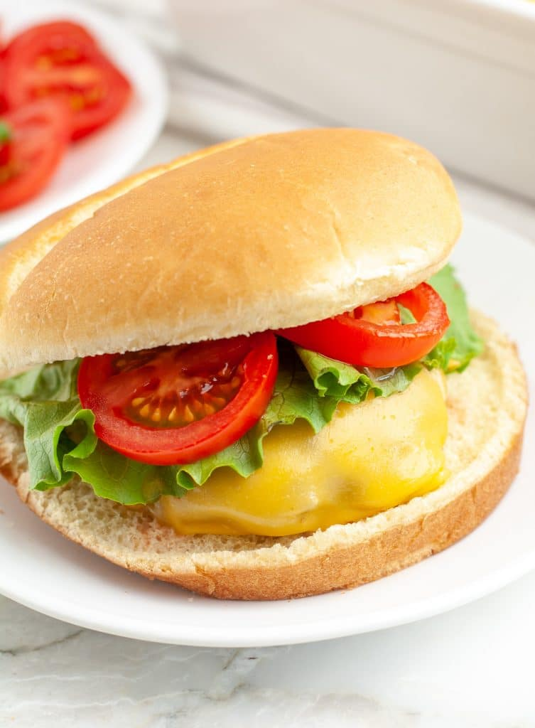 Cheeseburger on a bun with lettuce and tomato.