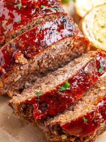 Sliced meatloaf on a board with toast.