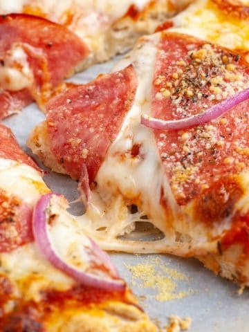 Cooked pizza slice with onion and salami.