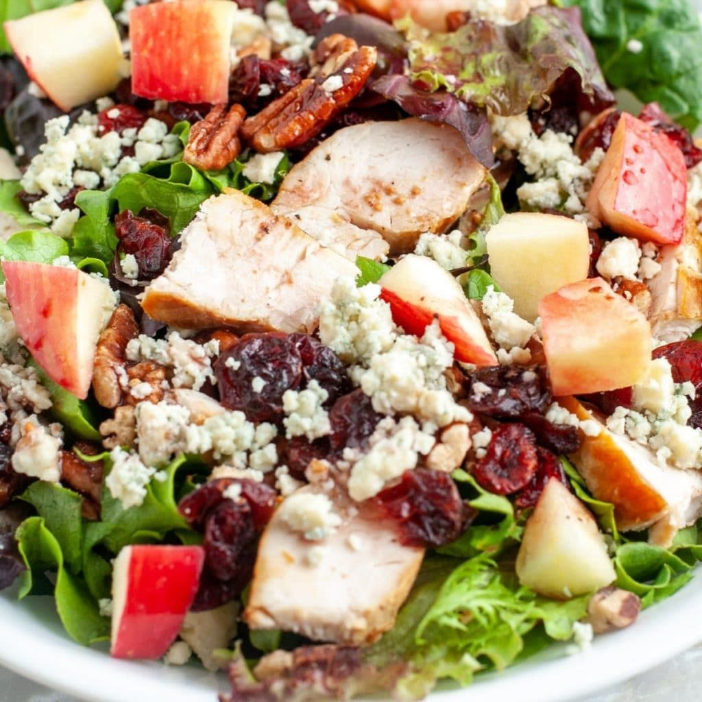 Bowl of salad with chicken and apple.