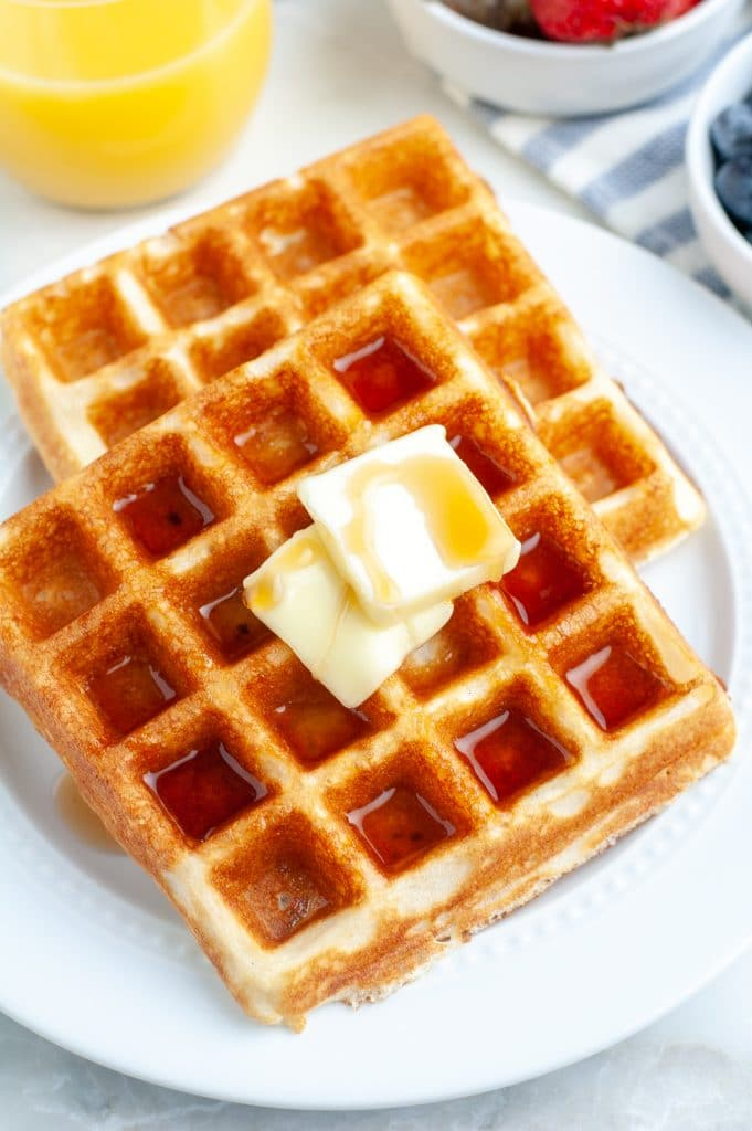 Plate of waffles with glass of orange juice.