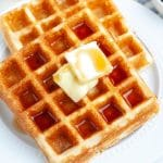 Plate of waffles with butter.